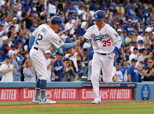 Dodgers right fielder Cody Bellinger (35) is greeted by third-base coach Dino Ebel (12) after Bellinger hit a solo home run in the sixth inning Sunday at Dodger Stadium in Los Angeles. (Photo by John Cordes/Icon Sportswire via Getty Images)