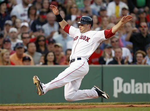 Boston Red Sox's Daniel Nava begins to slide as he scores on a hit by Dustin Pedroia in the second inning of a baseball game against the Atlanta Braves in Boston, Saturday, June 23, 2012. (AP Photo/Michael Dwyer)