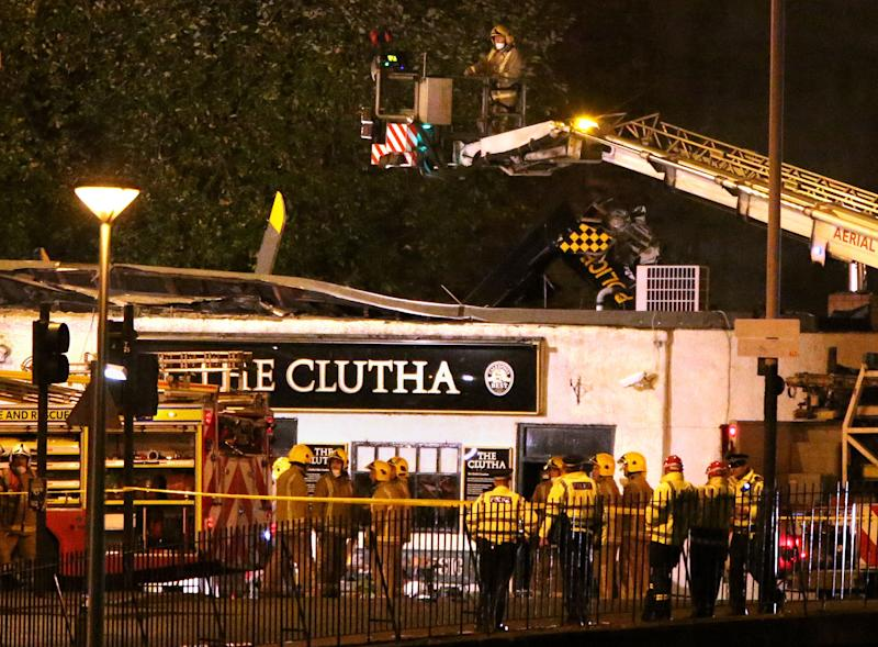 Police officers and firefighters inspect the damage of a helicopter crash, at a pub in Glasgow early Saturday Nov. 30, 2013. The police helicopter crashed late Friday night into the roof of a popular pub in Glasgow, Scotland, leaving the building littered with debris and emergency crews scrambling to the scene. (AP Photo /PA, Andrew Milligan) UNITED KINGDOM OUT, NO SALES, NO ARCHIVES