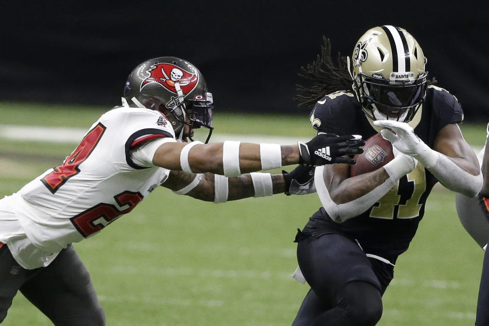 New Orleans Saints running back Alvin Kamara, right, runs against Tampa Bay Buccaneers cornerback Carlton Davis during the first half of an NFL divisional round playoff football game, Sunday, Jan. 17, 2021, in New Orleans. (AP Photo/Butch Dill)