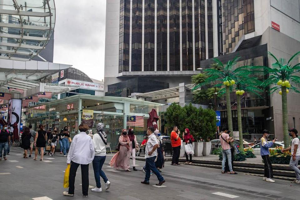 People are seen wearing protective masks as they walk along the Bukit Bintang shopping area during Phase One of the National Recovery Plan in Kuala Lumpur on September 4, 2021. — Picture by Firdaus Latif