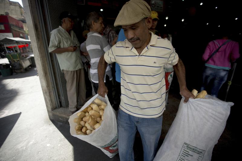 <p> In this March 17, 2017 photo, an employee of the Minka state-run bakery carries bags of bread to be distributed to state-run grocery stores in Caracas, Venezuela. Agents from the National Superintendent of Fair Prices raided Mansion's Bakery last week and accused the owners of hoarding scarce sacks of government-imported flour, saying the subsidized goods should have been used to make price-regulated loaves but instead was turned into more expensive croissants and sweet rolls. (AP Photo/Fernando Llano) </p>