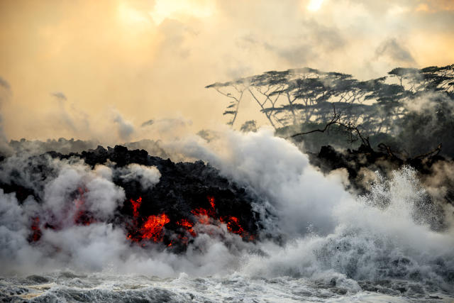 <p>Lava pours into surrounding waters, causing steam to rise. (Photo: CJ Kale/Caters News) </p>