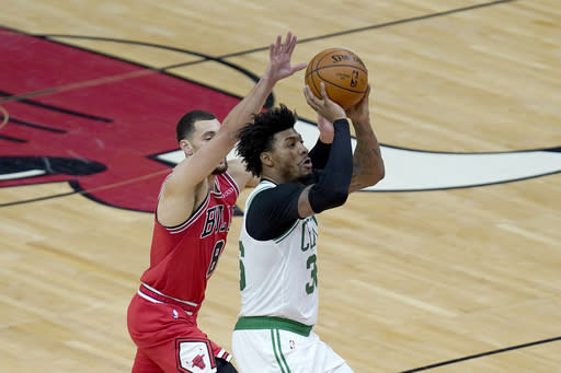 Boston Celtics' Marcus Smart (36) shoots past Chicago Bulls' Zach LaVine during the first half of an NBA basketball game Monday, Jan. 25, 2021, in Chicago. (AP Photo/Charles Rex Arbogast)