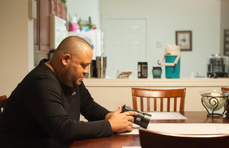 Delgado, in his home, looks at his camera. He took up photography after the Pulse shooting as a way to cope with his PTSD. (Chris McGonigal/HuffPost)