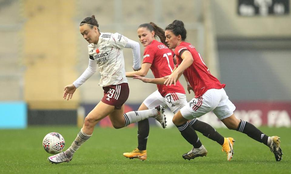 Caitlin Foord of Arsenal is challenged by Jess Sigsworth and Ona Batlle of Manchester United.