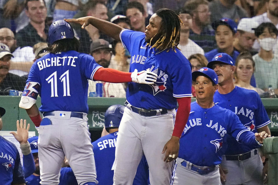 Toronto Blue Jays' Bo Bichette (11) is congratulated by Vladimir Guerrero Jr. after his two-run home run against the Boston Red Sox in the fifth inning of a baseball game at Fenway Park, Monday, July 26, 2021, in Boston. (AP Photo/Charles Krupa)