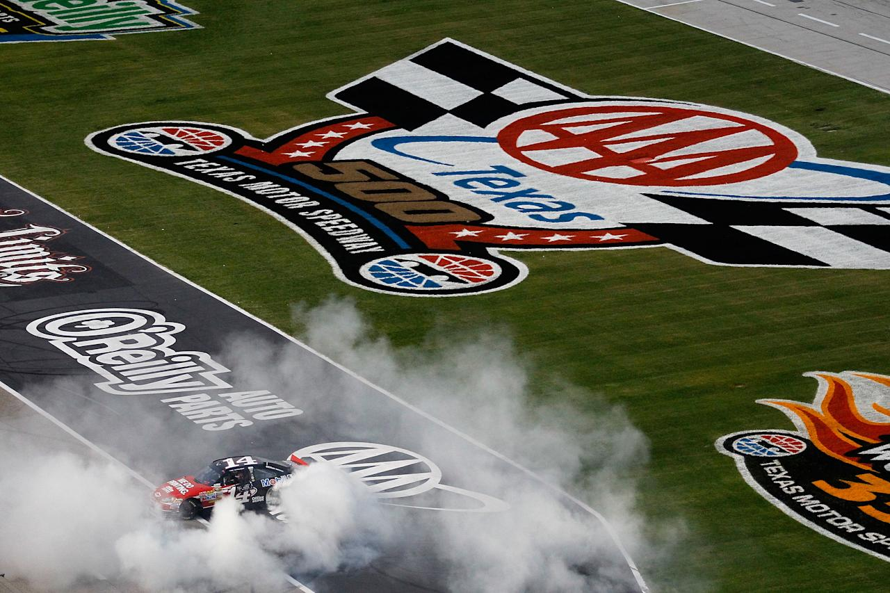 FORT WORTH, TX - NOVEMBER 06:  Tony Stewart, driver of the #14 Office Depot/Mobil 1 Chevrolet, performs a burnout in celebration of winning the NASCAR Sprint Cup Series AAA Texas 500 at Texas Motor Speedway on November 6, 2011 in Fort Worth, Texas.  (Photo by Todd Warshaw/Getty Images for NASCAR)