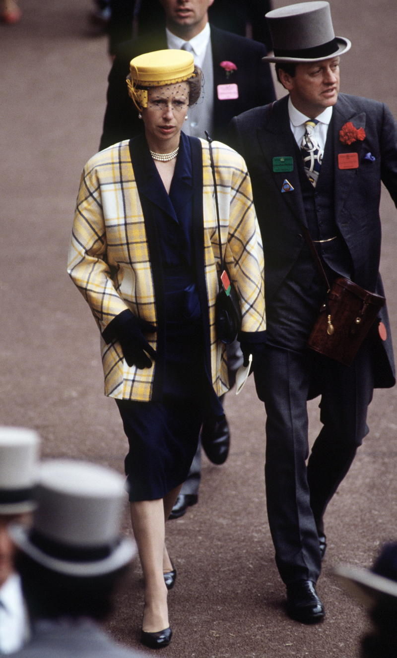 A photo of Princess Anne wearing a yellow plaid coat at Royal Ascot with Andrew Parker-Bowles in 1988.