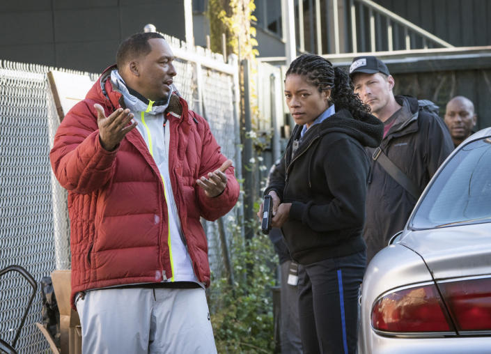 """This image released by Sony Pictures shows director Deon Taylor, left, and Naomie Harris on the set of Screen Gems """"Black and Blue."""" After making successful movies independently for 15 years, Hollywood is starting to take notice of Taylor. This year he has two major films in theaters. """"The Intruder"""" became a solid hit in May, and his police thriller """"Black and Blue"""" opens nationwide Thursday. (Alan Markfield/Sony Pictures via AP)"""