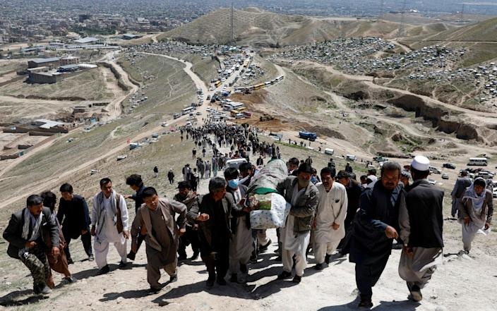 Men carry the coffins of victim up to a hillside graveyard above Kabul for a mass burial - REUTERS