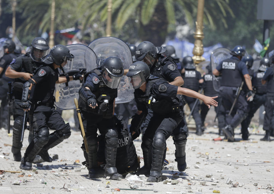 <p>Police pull an injured comrade out of clashes with protesters during a general strike against a pension reform measure, outside Congress in Buenos Aires, Argentina, Monday, Dec. 18, 2017. Union leaders complain the legislation, which already passed in the Senate, would cut pension and retirement payments as well as aid for some of poor families. (AP Photo/Natacha Pisarenko) </p>