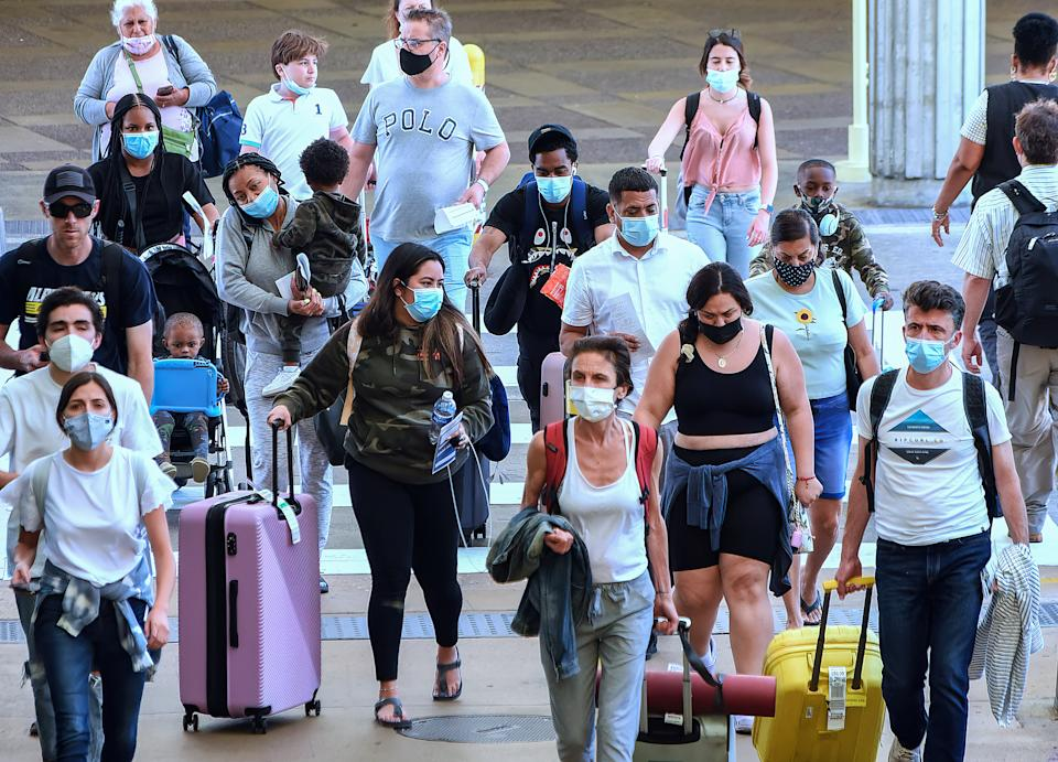 Travelers wearing protective face masks arrive at Orlando International Airport on the Friday before Memorial Day. (Paul Hennessy/SOPA Images/LightRocket via Getty Images)
