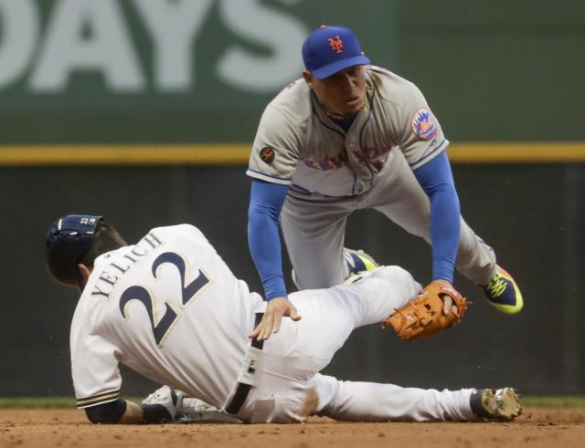 Milwaukee Brewers' Christian Yelich breaks up a double play as New York Mets' Asdrubal Cabrera makes a late throw on a ball hit by Ryan Braun during the third inning of a baseball game Thursday, May 24, 2018, in Milwaukee. (AP Photo/Morry Gash)