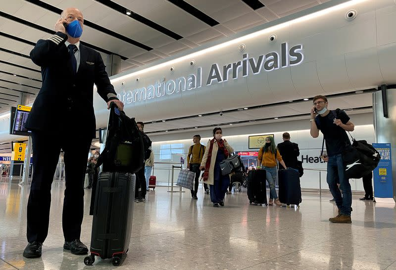 FILE PHOTO: A member of aircrew is seen wearing a protective face mask at Heathrow Airport, as Britain launches its 14-day quarantine for international arrivals, following the outbreak of the coronavirus disease (COVID-19), London, Britain
