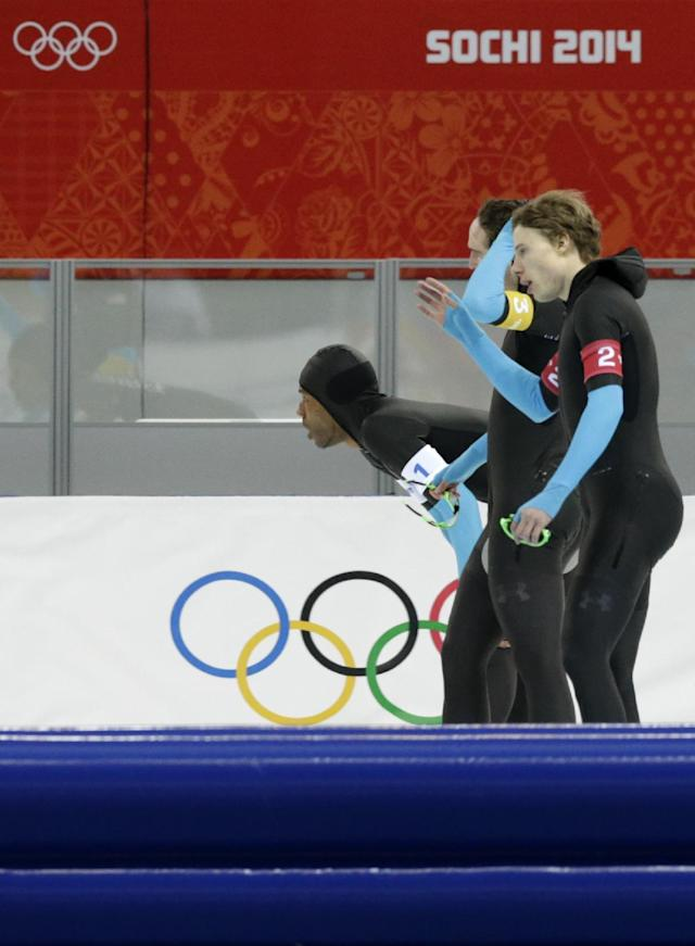 The U.S. speedskating team, Shani Davis, bending, Jonathan Kuck, background, and Brian Hansen catch their breath after competing in the men's speedskating team pursuit quarterfinals at the Adler Arena Skating Center during the 2014 Winter Olympics in Sochi, Russia, Friday, Feb. 21, 2014. (AP Photo/Matt Dunham)