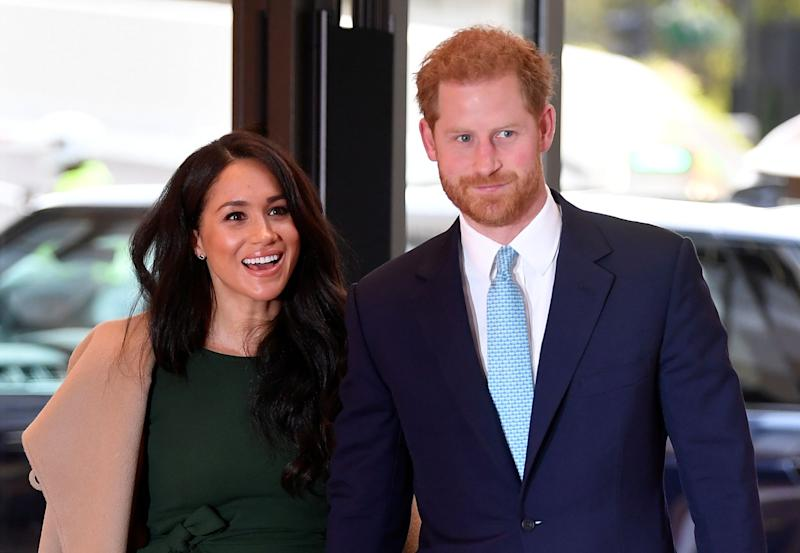 Meghan Markle and Prince Harry smile holding hands
