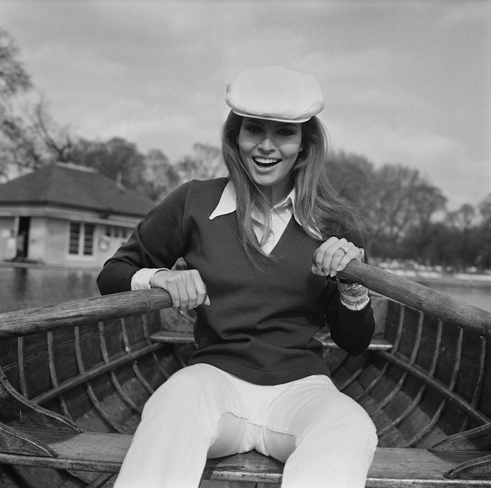 <p>Raquel Welch looks the part of a British boater with a collared shirt under a sweater, white trousers, and an ivy cap for an outing at the Serpentine in London. </p>
