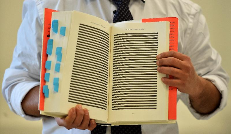 The younger brother of Mohamedou Ould Slahi poses with a copy of Mohamedou's prison memoir 'Guantanamo Diary' open to show pages that were redacted by the US government in London on January 20, 2015 (AFP Photo/Beb Stansall)