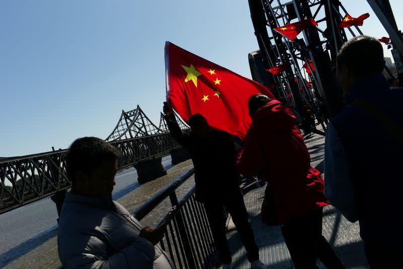 FILE PHOTO: Chinese visitor poses for picture with a Chinese flag on the Broken Bridge near the Friendship Bridge which connects North Korea's Sinuiju and China over the Yalu river, in Dandong