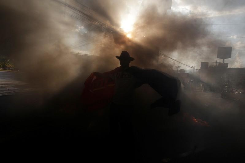 "A demonstrator is seen amidst smog during a protest against the government of president Juan Orlando Hernandez, whose brother Juan Antonio ""Tony"" Hernandez was found guilty of U.S. drug trafficking charges, in Tegucigalpa"