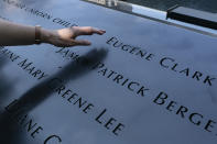 """Désirée Bouchat reaches towards the inscribed name of James Patrick Berger at the National September 11 Memorial, Friday, Aug. 6, 2021, in New York. She last saw her co-worker on the 101st floor of the trade center's south tower. Nearly 180 Aon Corp. workers perished on Sept. 11, 2001, including Berger. """"Some days, it feels like it happened yesterday,"""" Bouchat says. (AP Photo/Mark Lennihan)"""
