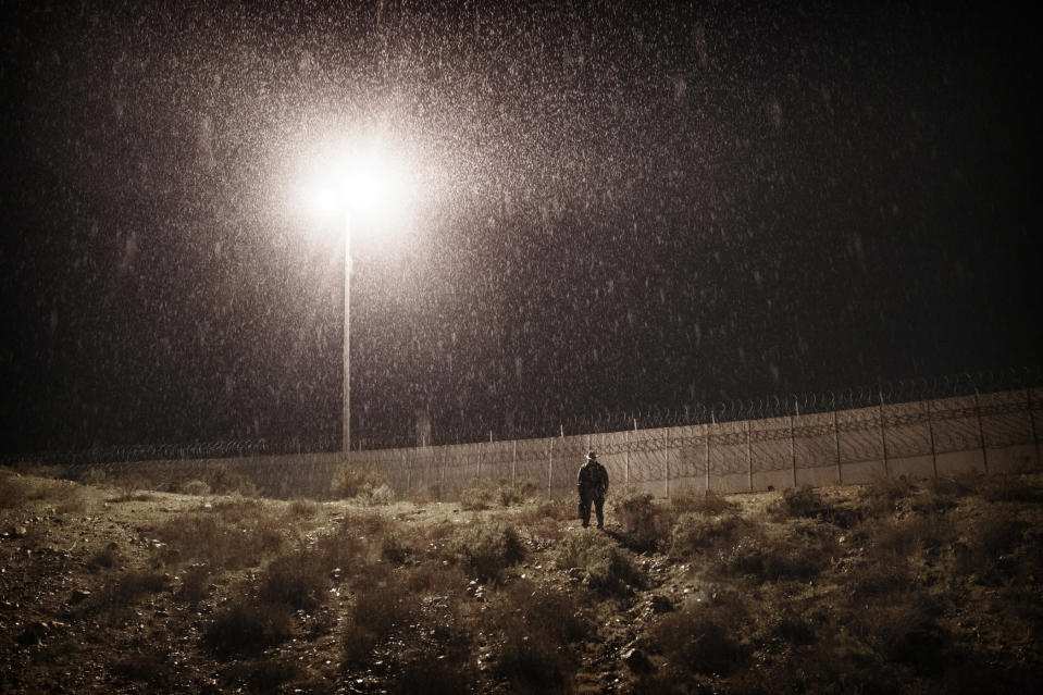 A U.S. Border Protection officer stands under the rain as he watches the border fence between the U.S. side and San Diego, Calif., from Tijuana, Mexico, Tuesday, Jan. 1, 2019. Discouraged by the long wait to apply for asylum through official ports of entry, many migrants from recent caravans are choosing to cross the U.S. border wall and hand themselves in to border patrol agents. (AP Photo/Daniel Ochoa de Olza)