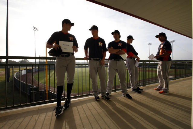 Houston Astros pitcher Mark Appel, left, and others, line up to have their picture taken on photo day at their spring training baseball facility, Friday, Feb. 21, 2014, in Kissimmee, Fla. (AP Photo/Alex Brandon)