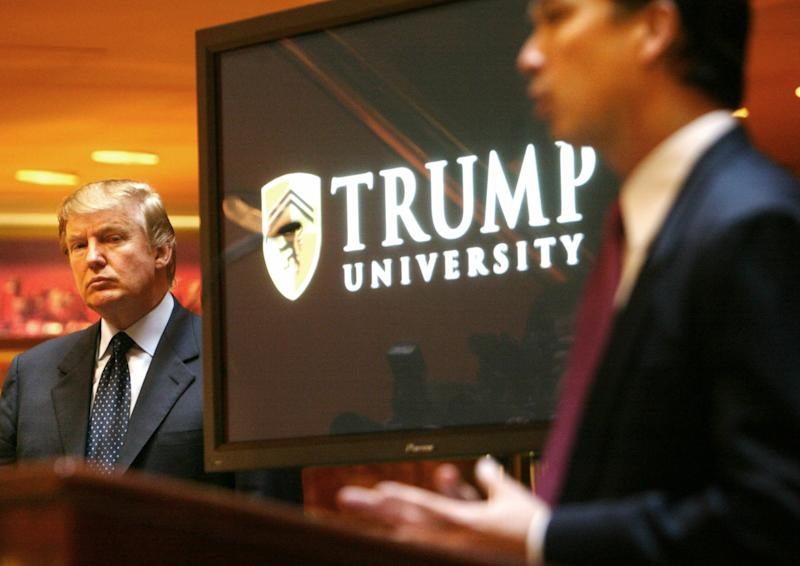 """FILE- In this May 23, 2005 file photo, real estate mogul and Reality TV star Donald Trump, left, listens as Michael Sexton introduces him at a news conference in New York where he announced the establishment of Trump University. New York Attorney General Eric Schneiderman is suing Trump for $40 million, saying that """"Trump University"""" didn't deliver on its advertised promise to make students rich, but instead steered them into expensive yet mostly useless seminars. (AP Photo/Bebeto Matthews, File)"""