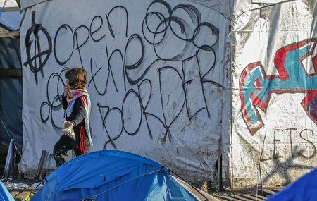 """A young migrant walks past graffiti reading """"Open the border"""" in a muddy field at a camp of makeshift shelters for migrants and asylum-seekers from Iraq, Kurdistan, Iran and Syria, called the Grande Synthe jungle, near Dunkirk, France, January 25, 2016.  REUTERS/Yves Herman"""