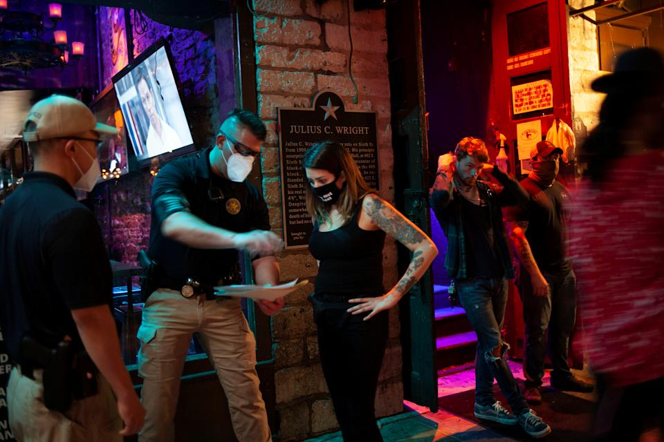 Lindsey Pettita, third from left, a bar manager at The Jackalope, a bar further down the block on Sixth Street, talks with agents from the Texas Alcoholic Beverage Commission as they check that bars are maintaining social distancing protocols to help slow the spread of the coronavirus disease (COVID-19), on the first day that bars in Texas were allowed to reopen after they were shut down in March, in Austin, Texas, U.S. May 22, 2020. Picture taken May 22, 2020. REUTERS/Nuri Vallbona