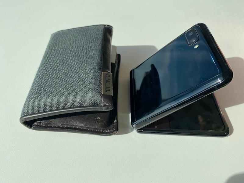 A physical Tumi wallet next to the Samsung Z Flip fold that folds like a wallet.