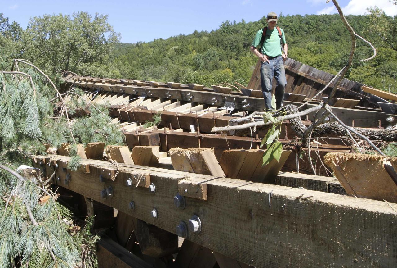 Teo Campbell stands on what used to be the bottom of the Bartonsville Covered Bridge over the Williams River, Monday, Aug. 29, 2011 in Rockingham, Vt . Heavy rains from Tropical Storm Irene tore the bridge out Sunday and carried it downstream. (AP Photo/Jim Cole)