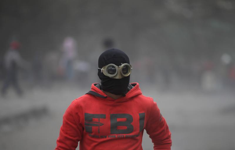 An Egyptian protester part of the Black Bloc, clashes with riot police, not seen, near Tahrir Square, Cairo, Egypt, Monday, Jan. 28, 2013. An unpredictable new element has entered Egypt's wave of political unrest, a mysterious group of black-masked young men calling themselves the Black Bloc. They present themselves as the defenders of protesters against the rule of President Mohammed Morsi, but Islamists have used them to depict the opposition as a violent force wrecking the nation. (AP Photo/Khalil Hamra)