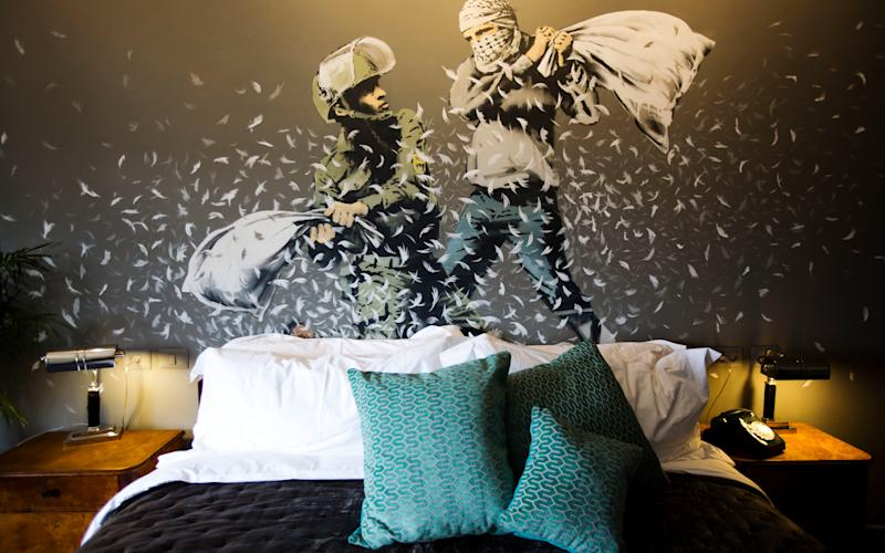 A Banksy wall painting showing Israeli border policeman and Palestinian in a pillow fight is seen in one of the rooms  - Credit: Dusan Vranic/AP