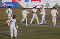 South Africa's George Linde, second right, celebrates with teammates after taking the wicket of Pakistan's Fawad Alam, left bottom, during the third day of the second cricket test match between Pakistan and South Africa at the Pindi Stadium in Rawalpindi, Pakistan, Saturday, Feb. 6, 2021. (AP Photo/Anjum Naveed)