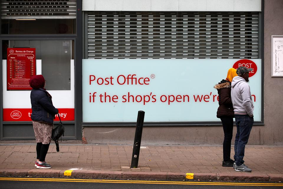 People maintain social distancing as they queue outside a post office in Wolverhampton city centre as the UK continues in lockdown to help curb the spread of the coronavirus.