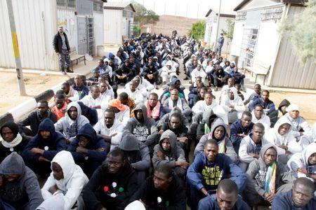 Illegal migrants, who have been detained after trying to get to Europe, sit in row on the ground of a detention camp in Gheryan, outside Tripoli