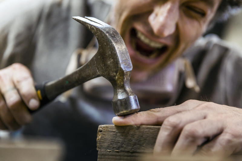 A photo of carpenter accidentally hit his finger with hammer. Mature craftsperson is crying in pain. He is screaming in workshop.