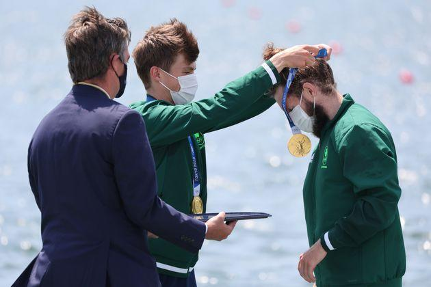 Ireland's Fintan McCarthy places a gold medal on teammate Paul O'Donovan at the medal ceremony for men's lightweight double sculls on July 28. (Photo: picture alliance via Getty Images)