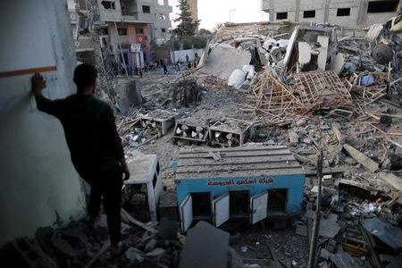 A Palestinian man looks at the remains of Hamas's TV station building that was destroyed by Israeli air strikes, in Gaza City November 13, 2018. REUTERS/Suhaib Salem