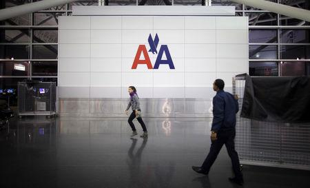 FILE PHOTO: People walk past an American Airlines logo on a wall at John F. Kennedy (JFK) airport in in New York November 27, 2013.  REUTERS/Carlo Allegri/File Photo