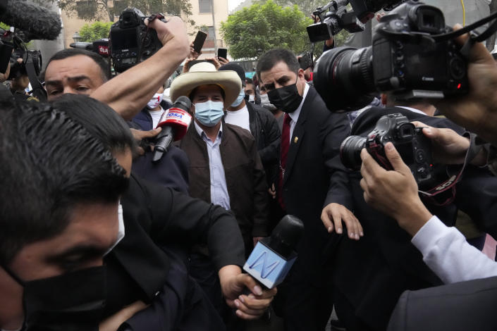 FILE - In this June 15, 2021 file photo, presidential candidate Pedro Castillo is surrounded by journalists as he arrives to his campaign headquarters to give a press conference in Lima, Peru. After more than a month since the election Castillo is expected to be named president, even after opponent Keiko Fujimori has claimed electoral fraud . (AP Photo/Martin Mejia, File)