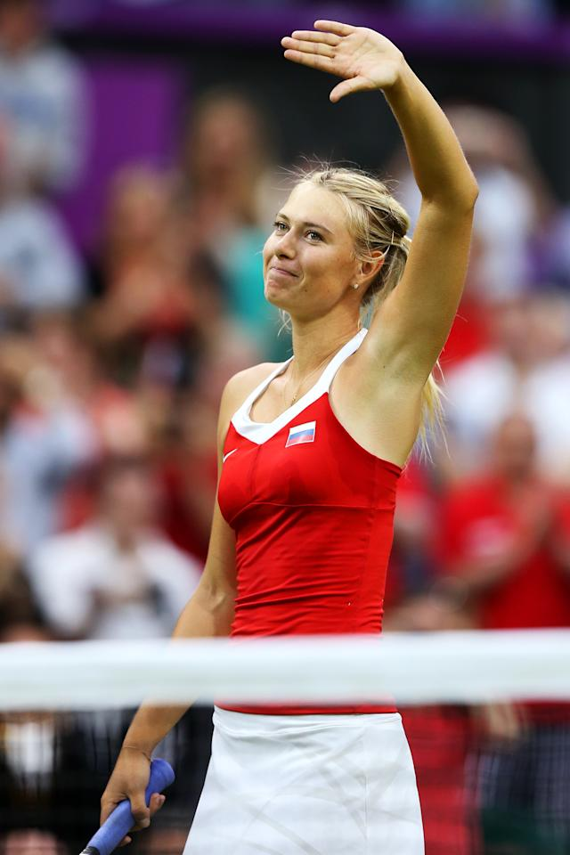 LONDON, ENGLAND - JULY 29:  Maria Sharapova of Russia waves to the crowd as she celebrates match point during the Women's Singles Tennis match against Shahar Peer of Israel on Day 2 of the London 2012 Olympic Games at the All England Lawn Tennis and Croquet Club in Wimbledon on July 29, 2012 in London, England.  (Photo by Ezra Shaw/Getty Images)