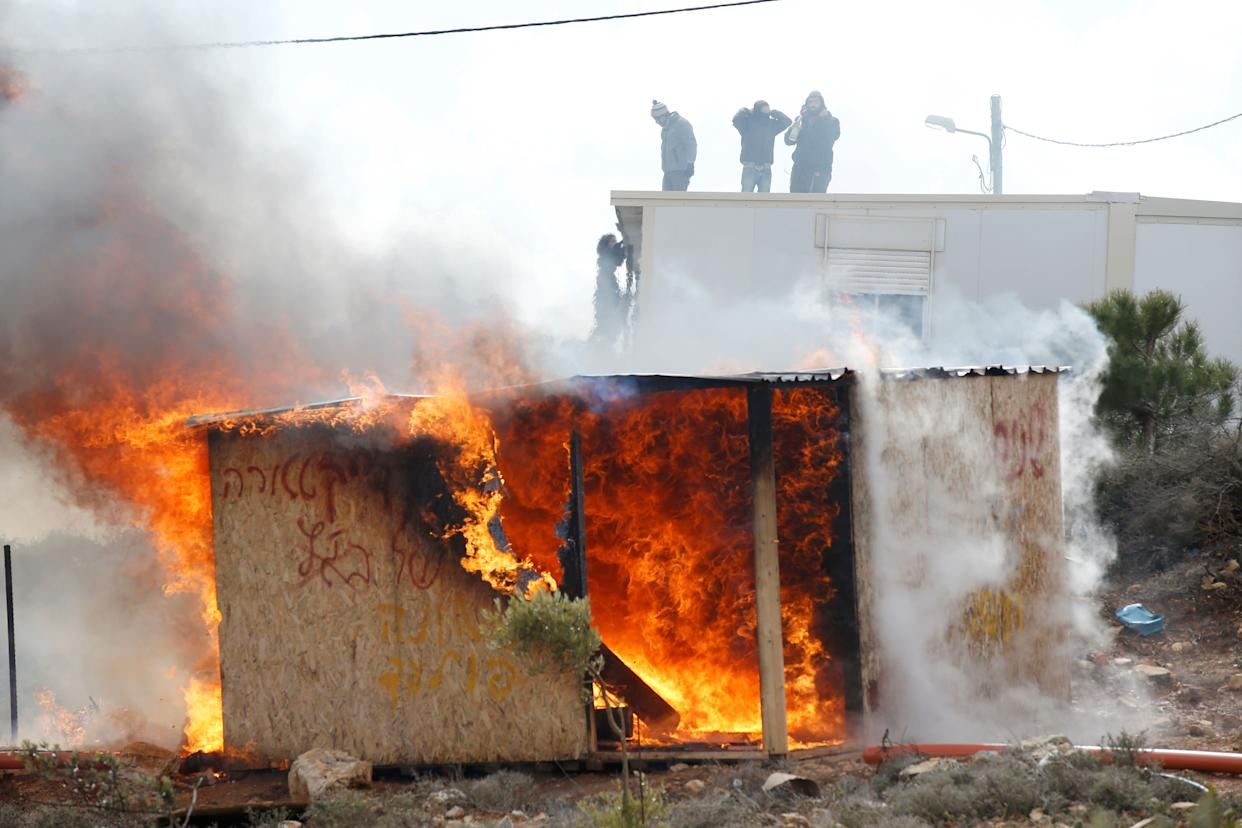 Protesters stand atop a roof as a shed burns during an eviction by Israeli police of residents from the Israeli settler outpost of Amona.