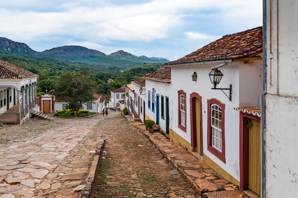 Looking down the stone paved streets of the historic quarter of Tiradentes, from the Matriz de Santo Antonio church on the top of the hill, one can take in the colonial architecture of Brazil, when still under Portuguese rule, with the mountain ridge in the backdrop, from where much of the gold and precious stones were mined in the former colony, and then sent to Portugal. Tiradentes is a city who's hostoric city centre is still preserved and mantained, as it was in the heydays of one of the wealthiest cities of Brazil. Today, thanks to the well kept facades, it is a major tourist attraction for its architectural and historic values.