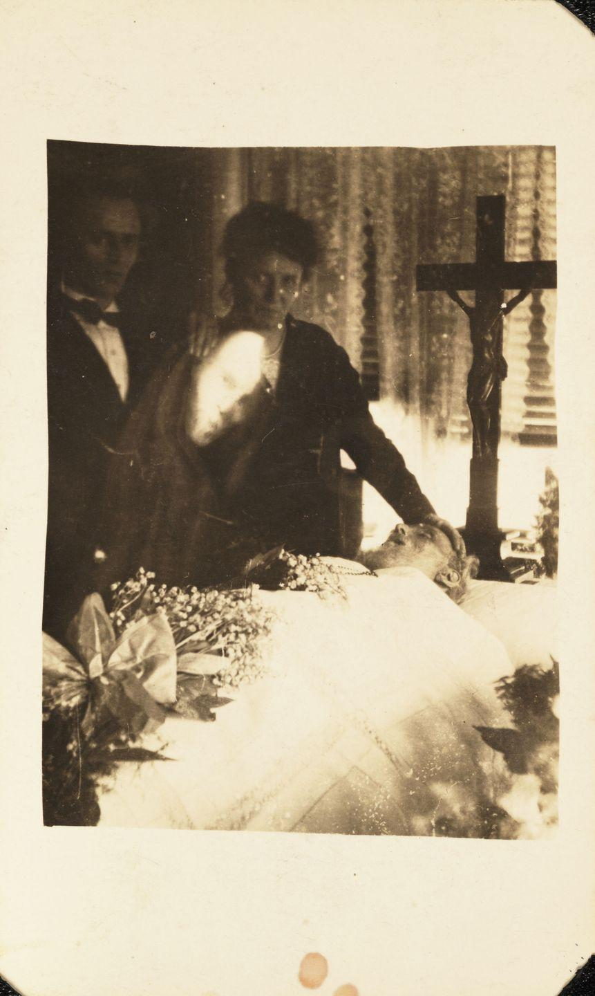 "<p>A woman stands with her hand on the forehead of a deceased loved one, while a ghostly face watches over. According to BBC<em>, </em><a href=""https://www.bbc.com/future/article/20150629-the-intriguing-history-of-ghost-photography"" rel=""nofollow noopener"" target=""_blank"" data-ylk=""slk:spirit photography was popularized during the mid-19th century"" class=""link rapid-noclick-resp"">spirit photography was popularized during the mid-19th century</a>, as cameras became readily available. The technique used multiple exposures to create the appearance of ghostly figures. </p>"