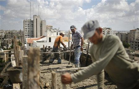 Palestinian workers flatten cement on the roof of a building under construction in Gaza City September 22, 2013. REUTERS/Mohammed Salem