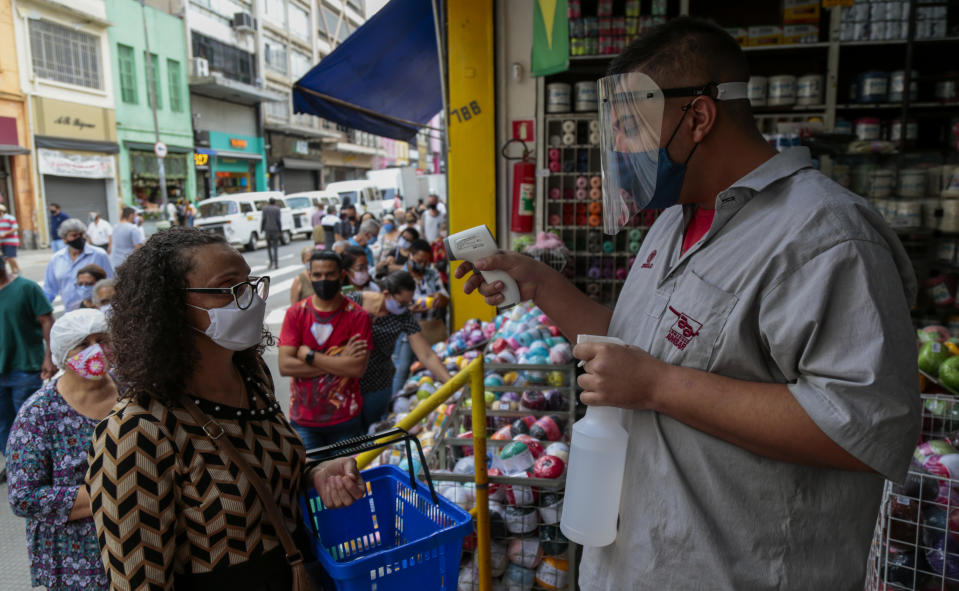 SAO PAULO, BRAZIL - JUNE 10: A customer wearing a mask has their temperature measured in downtown Sao Paulo during the fist day of commerce opening since the beginning of quarantine due to the coronavirus (COVID-19) pandemic on June 10, 2020 in Sao Paulo, Brazil. Establishments in the city of Sao Paulo will be able to operate only 4 hours a day, between 11 am and 3 pm, and must follow hygiene standards. (Photo by Miguel Schincariol/Getty Images)