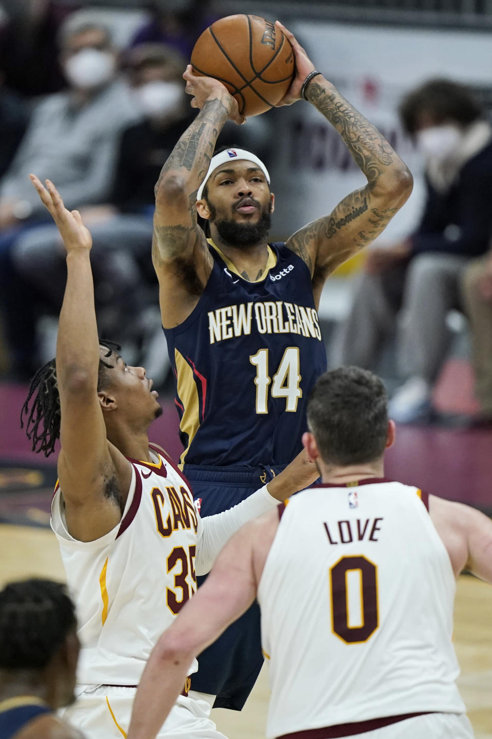 New Orleans Pelicans' Brandon Ingram, center, shoots over Cleveland Cavaliers' Isaac Okoro, left, and Kevin Love, right, in the second half of an NBA basketball game, Sunday, April 11, 2021, in Cleveland. (AP Photo/Tony Dejak)